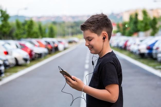 Menino do adolescente na roupa ocasional que escuta a música em seu telefone móvel. Foto Premium
