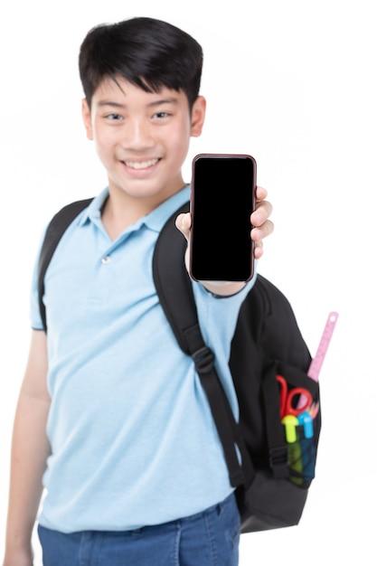 Menino do estudante com a trouxa e os artigos de papelaria que guardam o telefone celular. Foto Premium