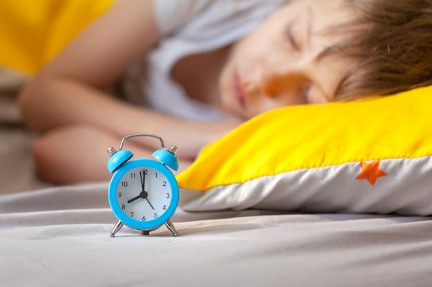 Menino dormindo na cama com um despertador perto de sua cabeça Foto Premium