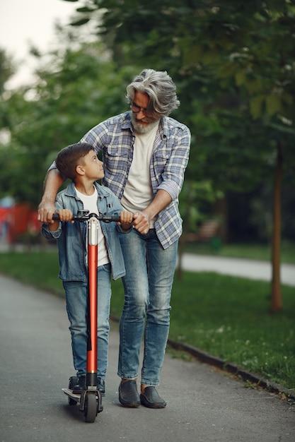 Menino e avô estão caminhando no parque. velho brincando com o neto. criança com scooter. Foto gratuita