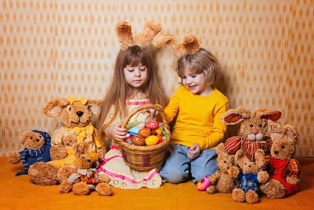 Menino e menina com as orelhas de coelho que sentam-se em torno de muitas lebres da palha e do luxuoso, estilo do vintage. Foto Premium