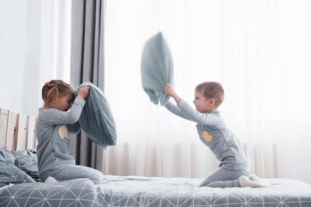 Menino e menina encenaram uma luta de travesseiros na cama do quarto. crianças travessas batem nos travesseiros. eles gostam desse tipo de jogo. Foto Premium