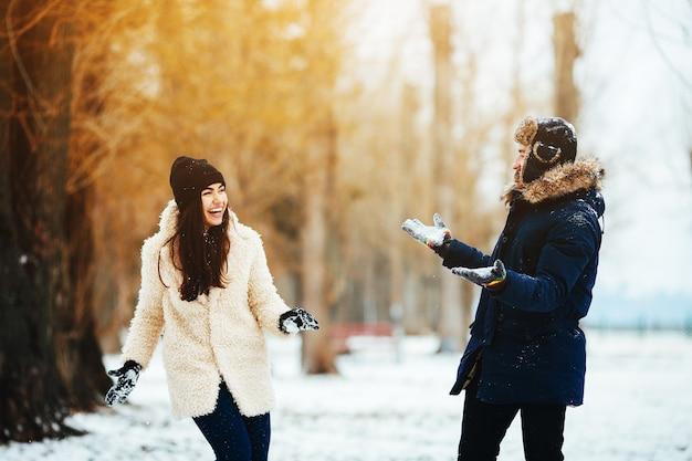 Menino e mulher brincando com neve em um parque coberto de neve Foto gratuita