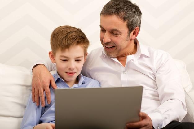 Menino e pai usando laptop juntos Foto Premium