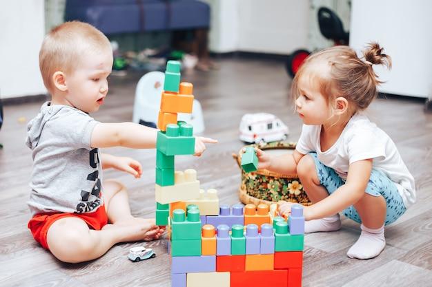 Menino e uma menina brincando de brinquedos em casa Foto Premium