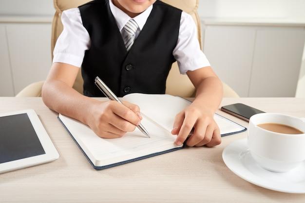 Menino elegantemente vestido irreconhecível, sentado na mesa no escritório e escrevendo no diário Foto gratuita