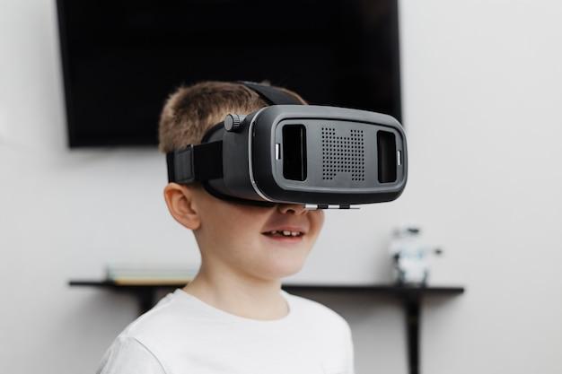 Menino em casa usando fone de ouvido de realidade virtual Foto gratuita