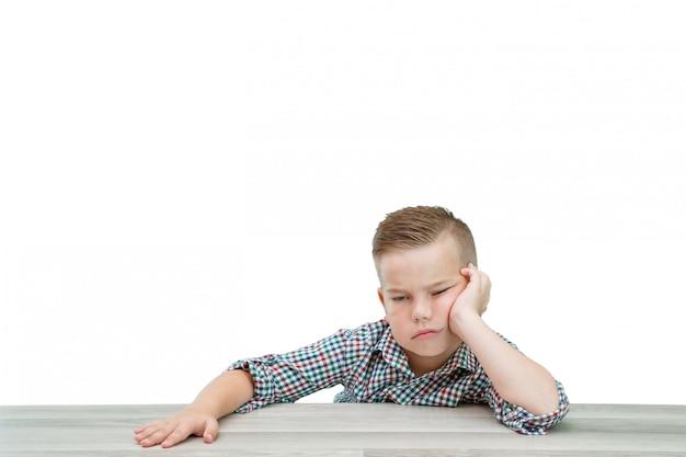 Menino em idade escolar caucasiano em uma camisa xadrez adormece sentado à mesa Foto Premium
