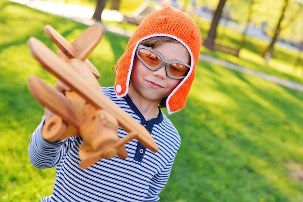 Menino, em, laranja, capacete, piloto, tocando, em, brinquedo, madeira, avião, contra, capim Foto Premium