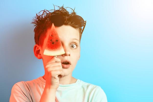 Menino, em, luz, camiseta, melancia, ligado, um, vara, fecha um olho, ligado, um, experiência azul Foto Premium