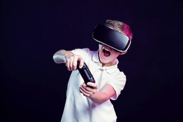Menino em óculos de realidade virtual, jogando com gamepad Foto Premium