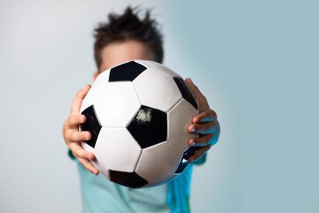 Menino, em, um, azul, t-shirt, segurando, um, bola futebol, em, seu, mãos, obscurecendo, seu, cabeça, ligado, um, experiência azul Foto Premium