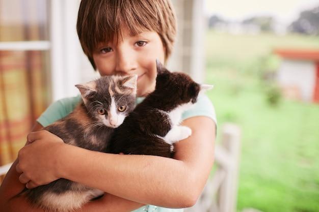 Menino encantador detém dois gatinhos em seus braços Foto gratuita