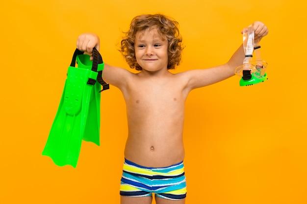 Menino encaracolado ruivo detém nadadeiras sobre fundo amarelo Foto Premium