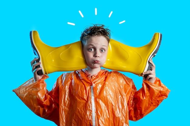 Menino engraçado em um casaco laranja com bochechas inchadas e botas de borracha no fundo azul Foto Premium