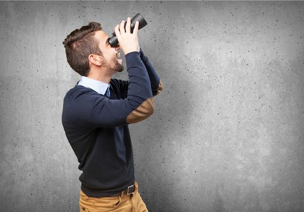 Menino espantado que usa seus binóculos Foto gratuita
