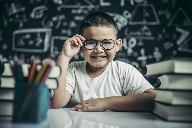 Menino estudando e segurando a perna de óculos em sala de aula. Foto gratuita
