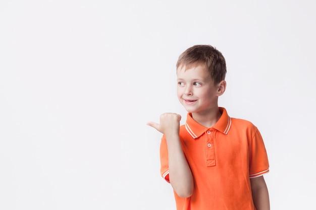 Menino feliz, apontando ao lado com o polegar no fundo branco Foto gratuita