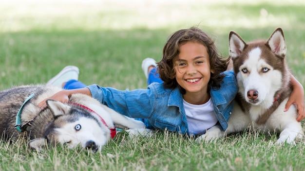 Menino feliz brincando com seus cachorros no parque Foto gratuita