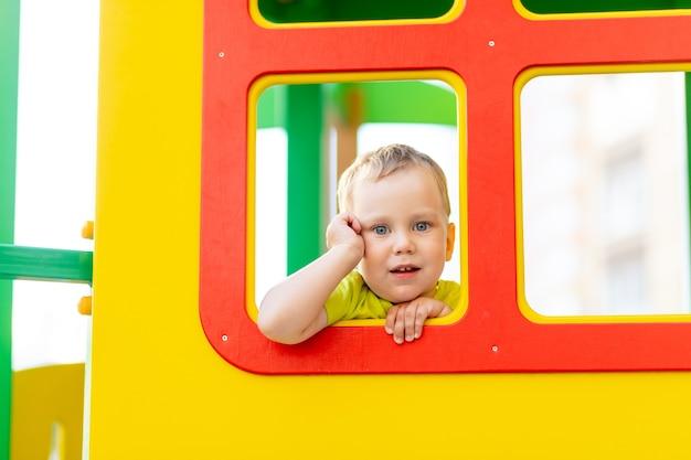 Menino feliz brincando no playground, menino olhando pela janela, estilo de vida infantil Foto Premium