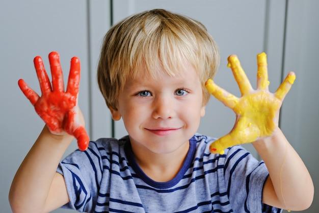 Menino feliz com três anos de idade, pinturas de dedo de pintura Foto Premium