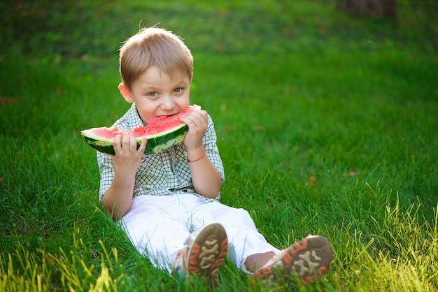 Menino feliz criança come melancia no verão Foto Premium