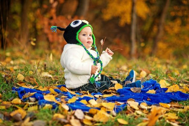 Menino feliz em roupas quentes mostra uma língua, sentado em uma manta azul e jogando em um gramado verde com folhas de outono no chão. Foto Premium
