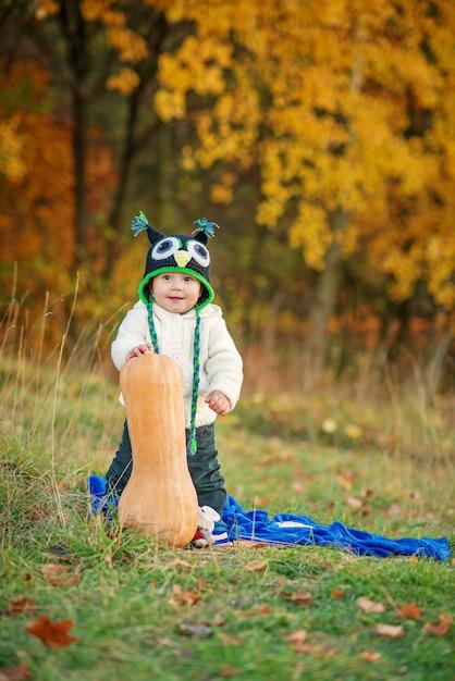 Menino feliz em um boné de malha e roupas quentes, ficar com abóbora no gramado entre as árvores de outono. Foto Premium