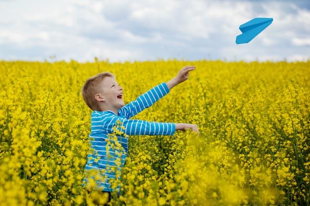 Menino feliz, inclinando-se e jogando o avião de papel azul no dia ensolarado no campo amarelo Foto Premium