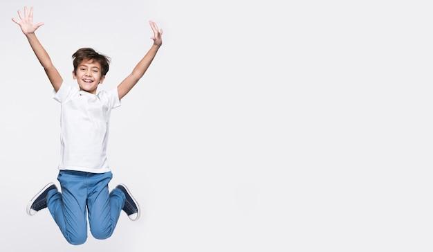 Menino feliz pulando com cópia-espaço Foto Premium