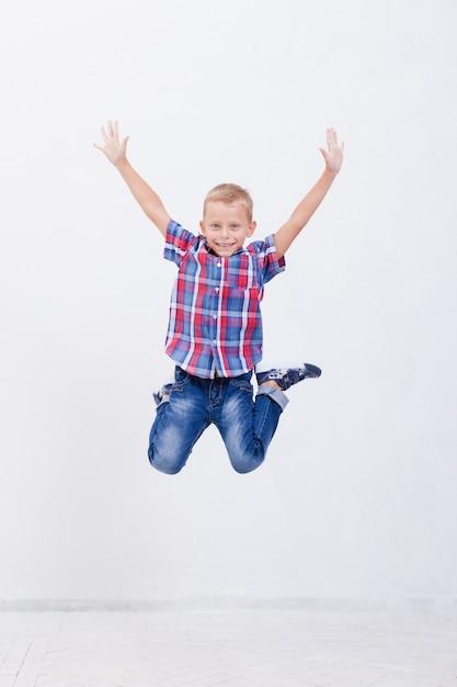 Menino feliz pulando em branco Foto gratuita