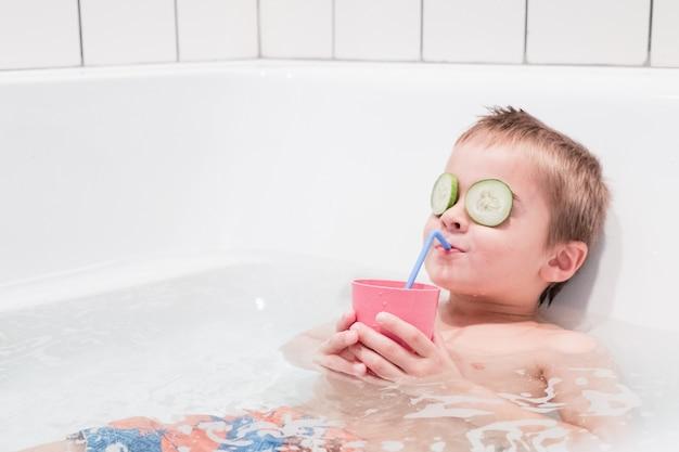Menino feliz tomando um banho relaxante em uma banheira de hidromassagem, bebendo suco Foto gratuita
