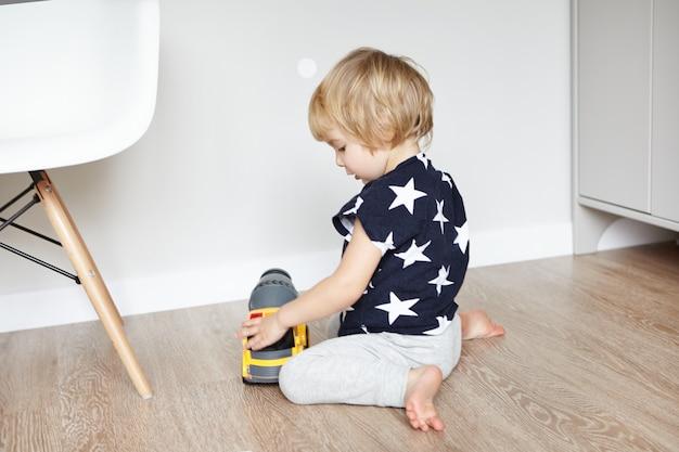Menino fofo com cabelo loiro, sentado no chão de madeira em seu quarto, segurando seu brinquedo favorito e sorrindo. criança se divertindo, brincando com o caminhão de plástico amarelo. aprendizagem precoce. Foto gratuita