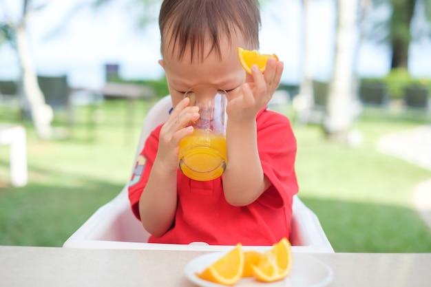 Menino fofo criança asiática sentada em uma cadeira alta segurando e bebendo uma bebida gelada de suco de laranja saboroso em um copo durante o café da manhã Foto Premium