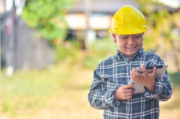 Menino garoto espera tablet usar capacete engenheiro construção Foto Premium