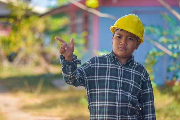 Menino garoto usar capacete engenheiro construção Foto Premium