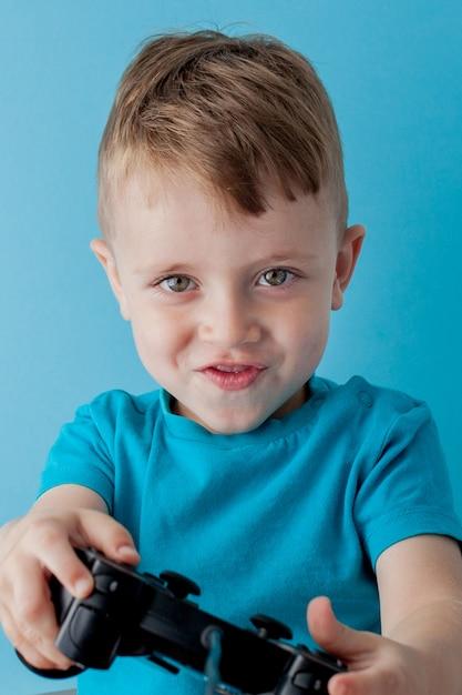 Menino garoto vestindo roupas azuis segurar joystick na mão para gameson fundo azul Foto Premium