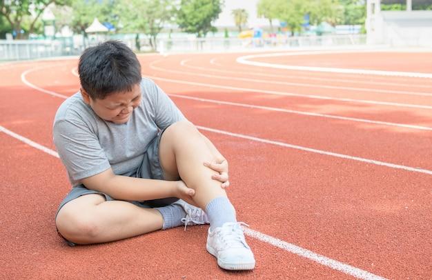 Menino gordo asiático segurando sua lesão na perna de esportes. músculo doloroso Foto Premium