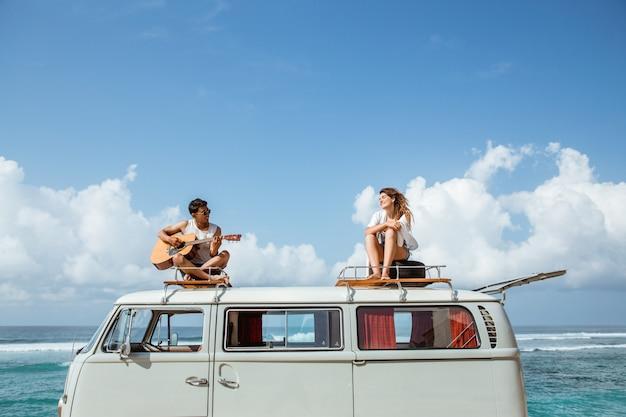 Menino hippie tocando violão com a namorada em cima do estilo retrô Foto Premium