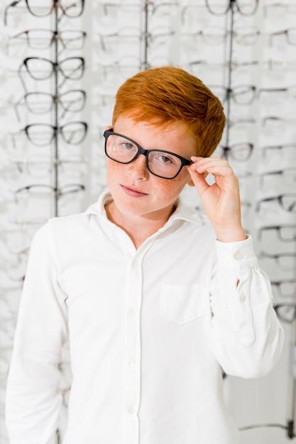 Menino inocente com pé de óculos de armação preta na loja de óptica Foto gratuita