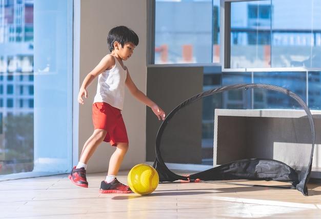 Menino jogador de futebol está pisando na bola na sala Foto Premium