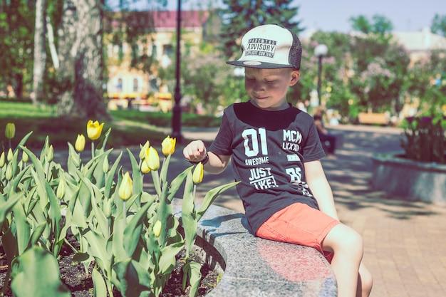 Menino jovem, cheiros, tulips, flor, em, primavera, jardim Foto Premium