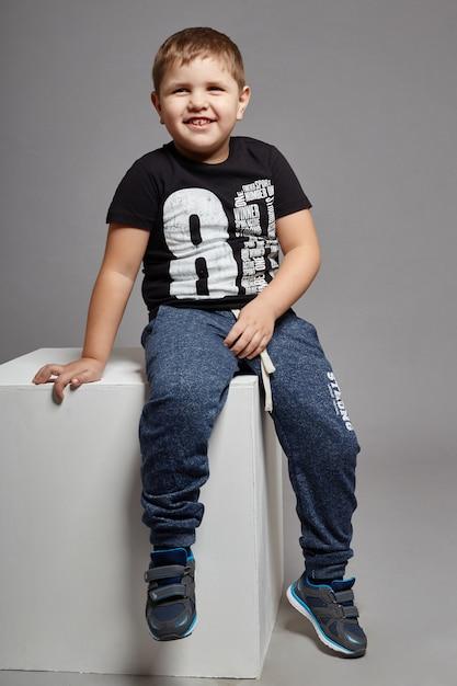 Menino jovem, criança, sorrindo, sentando, ligado, um, cubo branco Foto Premium