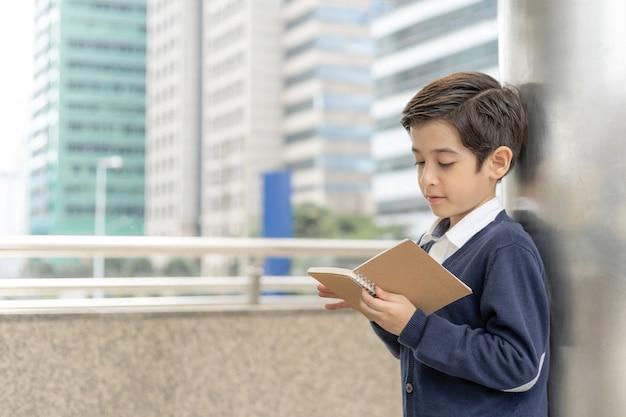 Menino jovem, leitura, um, livros, ligado, distrito negócio, urbano, conceito educação Foto Premium