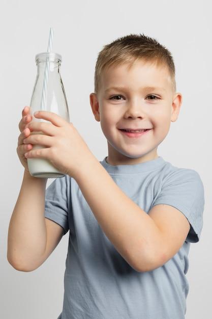 Menino jovem, segurando, garrafa leite, com, palha Foto gratuita