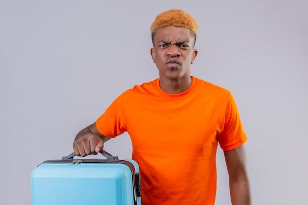 Menino jovem viajante descontente com uma camiseta laranja segurando uma mala e um rosto carrancudo em pé sobre uma parede branca Foto gratuita
