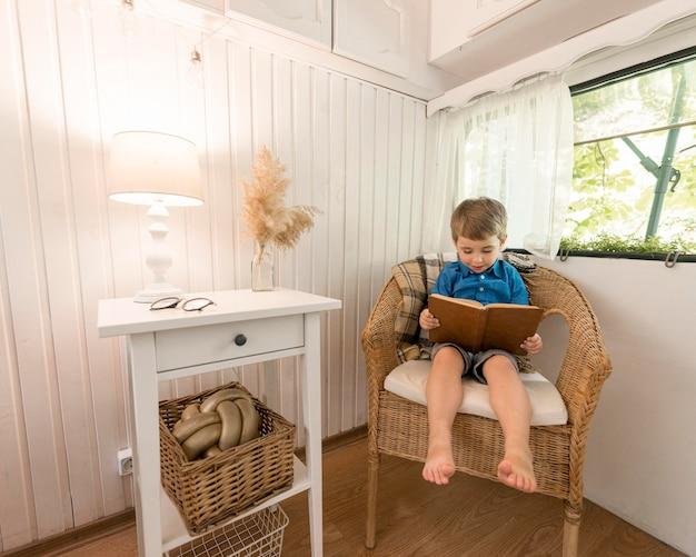 Menino lendo um livro sentado em uma poltrona Foto gratuita