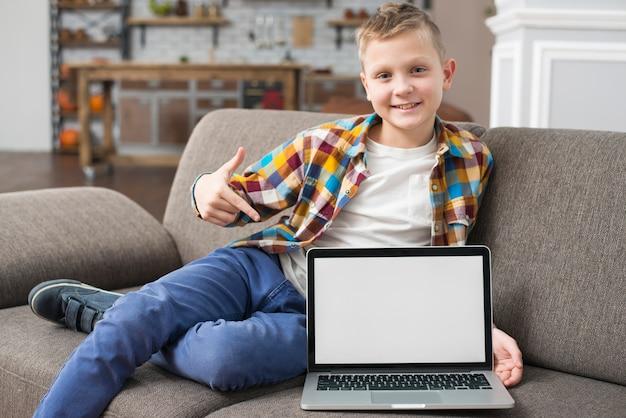 Menino, ligado, sofá, mostrando, laptop, tela Foto gratuita