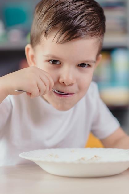 Menino lindo come mingau de leite. bebê fofo tomando café da manhã, sentado em uma mesa na cozinha em casa. Foto Premium