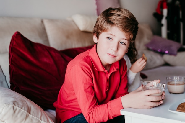 Menino lindo em casa tomando um lanche delicioso Foto Premium